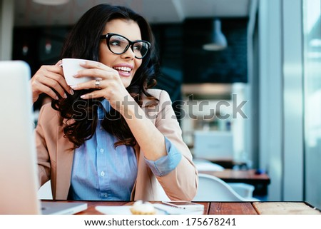 Young lady drinking coffe and looking through a window