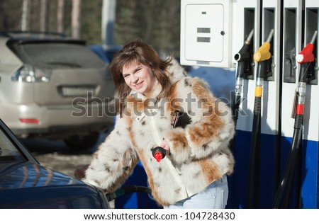 Young lady filling the car up at service station