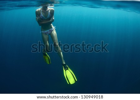 Young lady getting cold in a tropical sea and embracing herself during snorkeling. Horripelation on a skin!