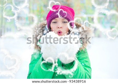 young lady happily playing in snow in winter