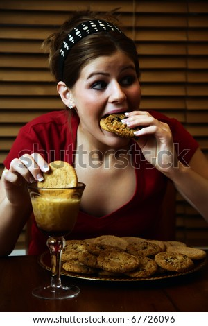 Young lady having a late night binge of cookies and milk.