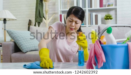 young lady householder wiping table hands in yellow protective gloves doing housework. beautiful female houseworker frowning cleaning up the living room at home in sunny day. asian woman lifestyle. #1242602392
