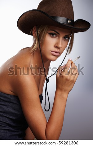 Young lady in a cowboy hat holding a cigarette in her hand