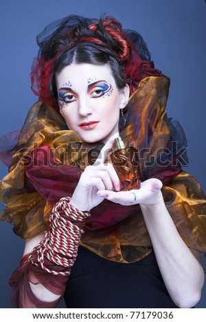 Young lady in artistic image with perfume bottle in her hands