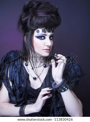 Young lady in black dress and with artistic make-up