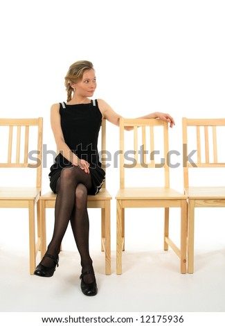Young lady in black sitting on a chair and waiting for someone.