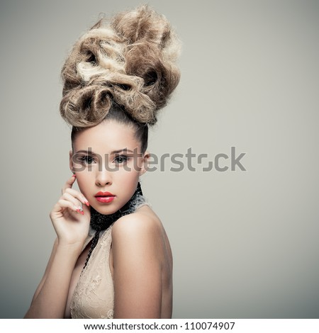 Young lady in fashionable dress posing on grey background