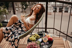 Young lady in floral skirt holds champagne glass and poses on terrace. Smiling girl sits next to table with fruits and white wine