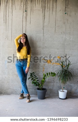 Stock Photo Young lady in yellow blouse and blue jeans