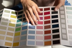 Young lady interior graphic designer illustrator think on project hold palette of various colored samples in hands. Woman client customer choose example of colors before apartment remodeling. Close up