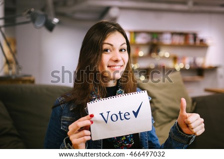 Young lady is agitating to vote in elections. Women brunette enjoys voting.\nBeautiful woman holding a sheet of paper with the \