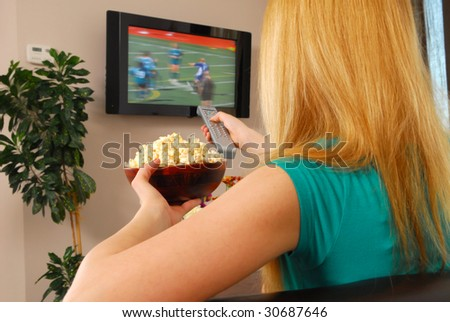 Young lady is sitting on a couch and watching a television