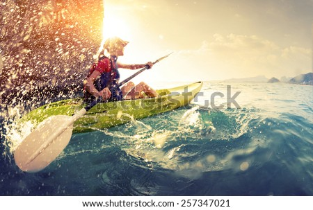 Young lady paddling hard the kayak with lots of splashes near the cliff at sunny day