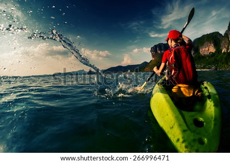 Young lady paddling hard the sea kayak with lots of splashes
