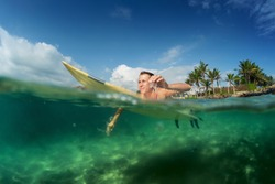 Young lady paddling on the surf board