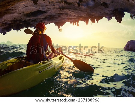 Young lady paddling the kayak from limestone cave towards open sea