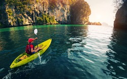 Young lady paddling the kayak in the calm bay with limestone mountains