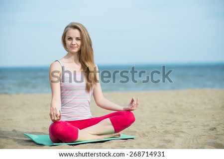 Stock Photo Young lady practicing yoga. Beautiful woman posing at the summer sand beach. Workout near ocean sea coast. Beautiful fit tan girl. Fitness model caucasian ethnicity outdoors. Weight loss exercise