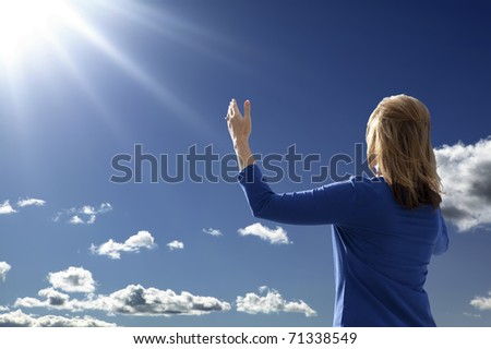 Young lady raising her arms in worship and praise while facing the rising sun.
