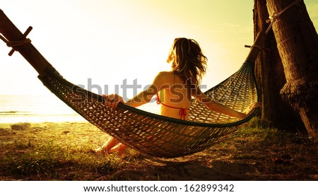Young lady relaxing in hammock on the tropical beach at sunset