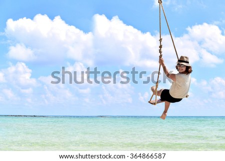 Young lady relaxing in the hammock on the sandy beach with view on remote tropical islands #364866587