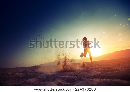 Young lady running in the desert at sunset