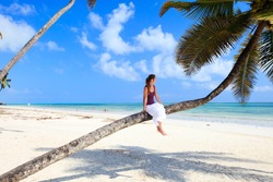 Young lady sitting on palm tree at tropical beach