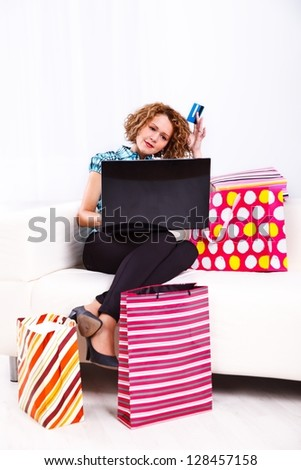 Young lady sitting on sofa at home with laptop, credit card and shopping bags, thinking