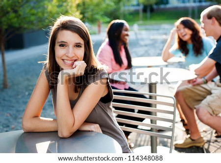 Young lady smiling with friends in the background talking