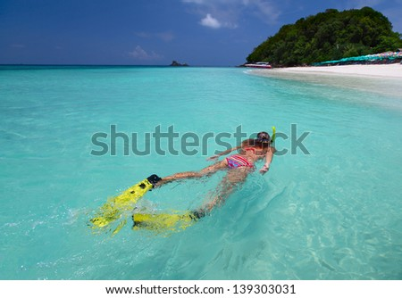 Young lady snorkeling in a turquoise sea at sunny day