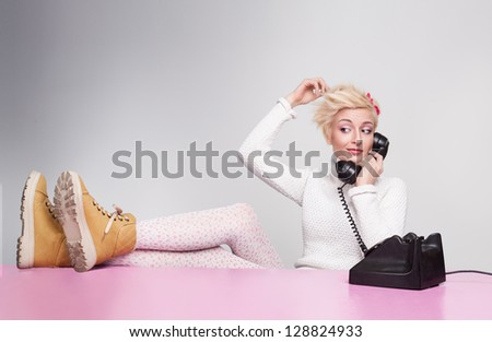 young lady speaking on the phone while her legs on the desk