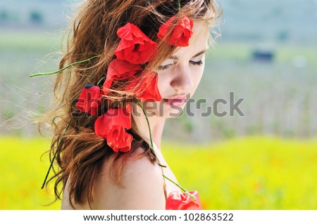 young lady standing with poppies in her hair