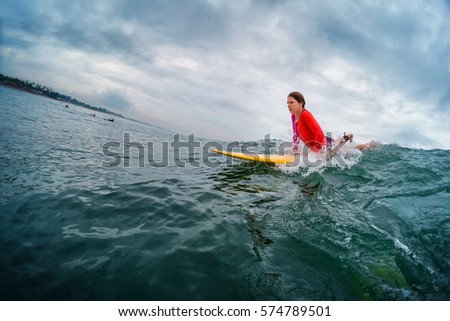 Young lady surfer trying to catch the wave in the ocean