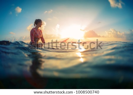 Young lady surfer waits the waves in ocean during sunrise with surf board.