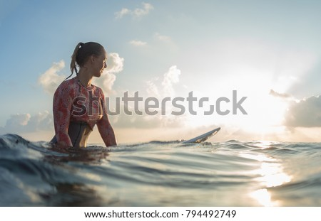 Young lady surfer waits the waves in the ocean during sunrise
