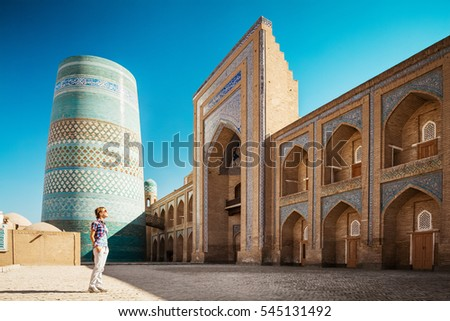 Young lady taking a picture of oriental buildings in Itchan Kala ancient town. Khiva, Uzbekistan