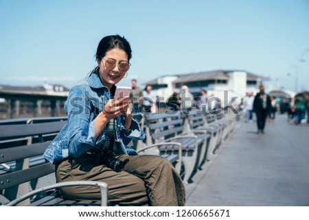 young lady travel photographer holding cellphone chatting with friends online app. beautiful woman using mobile searching guide book sitting on bench chair #1260665671