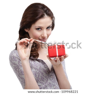 Young lady unwraps her present, isolated on white