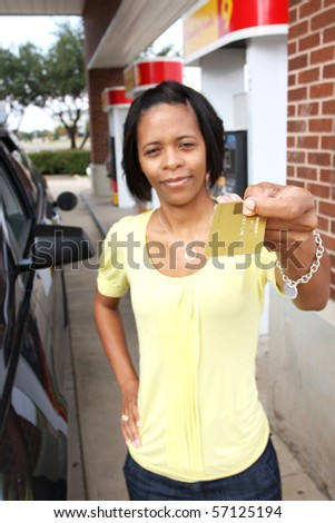 young lady using credit card to buy gas