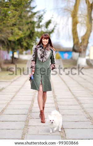 Young lady walking over her puppy