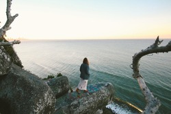 Young lady walks stand on look out of cliff edge to beach along coastline overlooking beach and sunset during dusk
