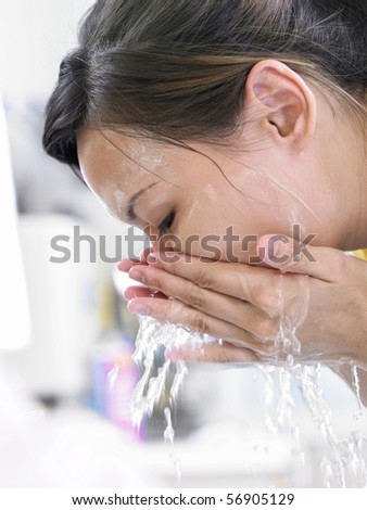 young lady washing her face