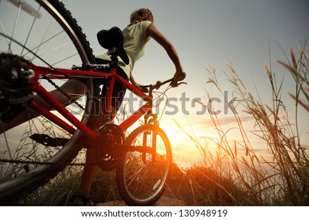Young Lady With Bicycle On A Rural Road With Grass