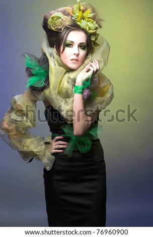 Young lady with creative visage and with feathers in her hands