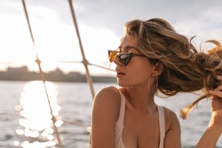Young lady with fluffy blonde hair in modern beach outfit and dark sunglasses posing in view of sea at sunshine and looking away