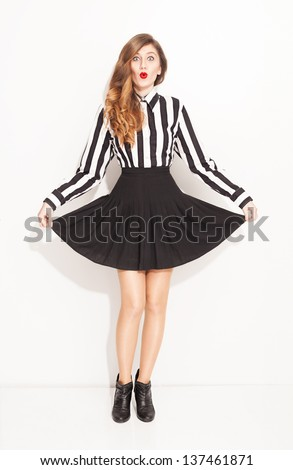 young lady with lined black and white shirt and pleated black skirt posing on white background