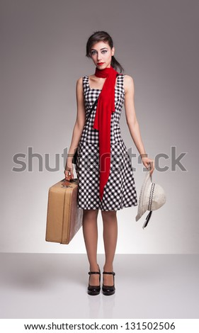 young lady with retro strap plaid dress carrying a suitcase on her hand and a hat on her other hand,waiting for her vehicle on grey background