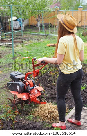 Young lady with rotating cultivating tiller tractor in the garden   #1383518654