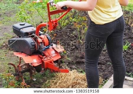 Young lady with rotating cultivating tiller tractor in the garden   #1383519158