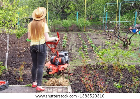 Young lady with rotating cultivating tiller tractor in the garden